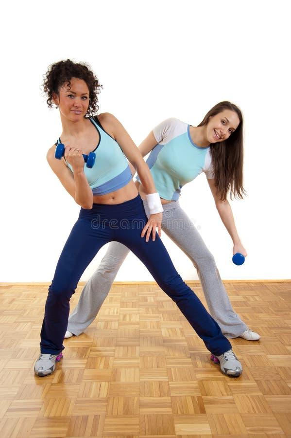 Duas meninas bonitas que exercitam com pesos fotos de stock royalty free
