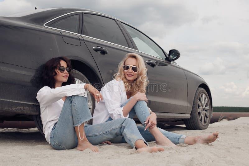 Duas meninas bonitas que sentam-se na máquina na praia foto de stock royalty free