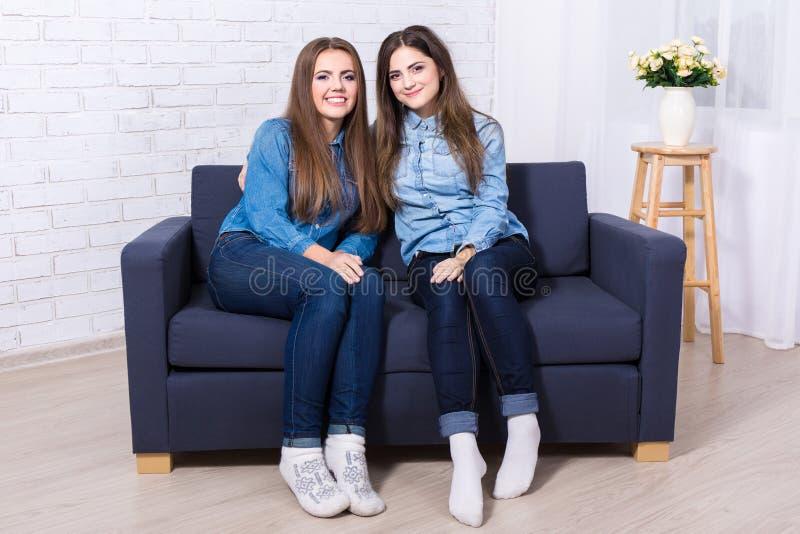 Duas meninas bonitas que sentam-se no sofá na sala de visitas imagens de stock royalty free