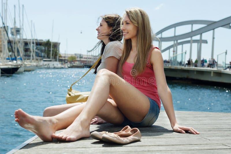 Duas meninas bonitas que sentam-se perto da ponte imagens de stock