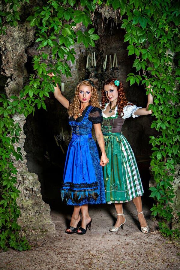 Duas meninas bonitas que vestem o Dirndl imagens de stock