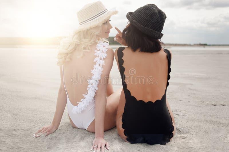 Duas meninas bonitas sentam-se na praia e apreciam-se a luz do sol fotografia de stock royalty free