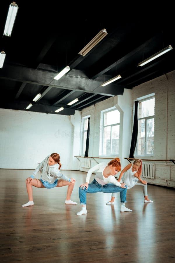 Duas meninas bonitos de squatting praticando da geração z na escola de dança foto de stock royalty free