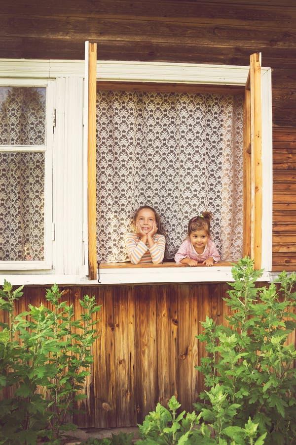 Duas meninas bonitos felizes que têm o divertimento na janela em casa no dia ensolarado fotos de stock