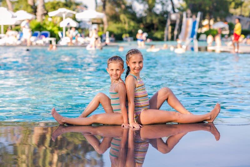 Duas meninas bonitos na piscina imagem de stock royalty free