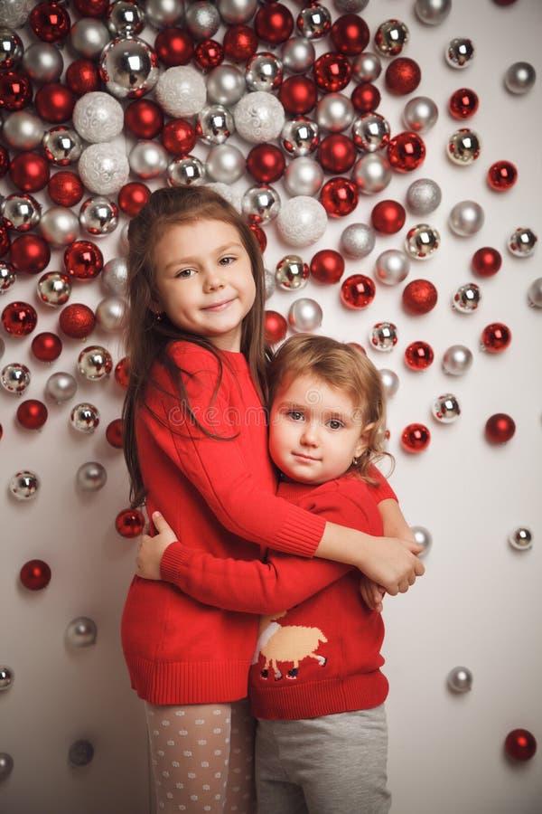 Duas meninas bonitos pequenas no fundo das bolas do Natal fotos de stock