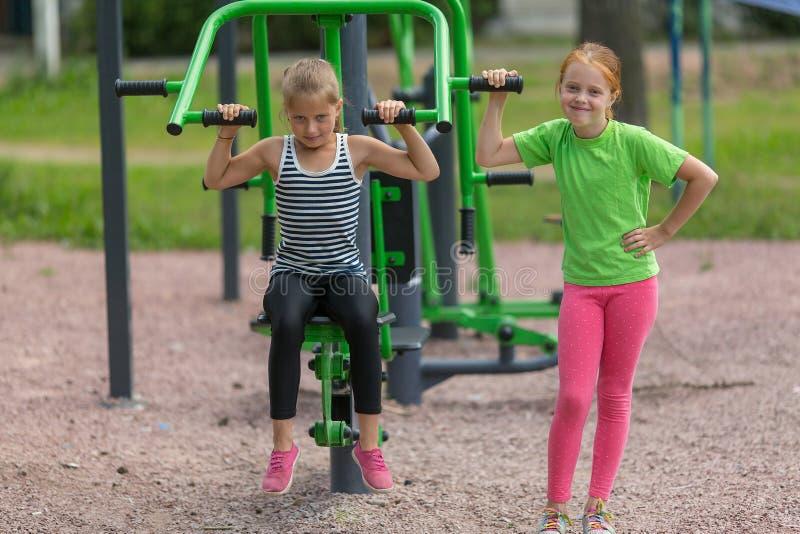 Duas meninas bonitos pequenas são contratadas no equipamento da aptidão fotos de stock