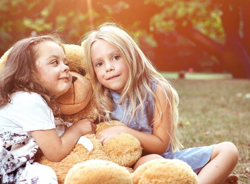 Duas meninas bonitos que abraçam um urso de peluche enorme fotos de stock