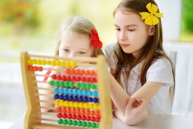 Duas meninas bonitos que jogam com ábaco em casa Irmã mais velha que ensina seu irmão contar Criança esperta que aprende contar imagens de stock