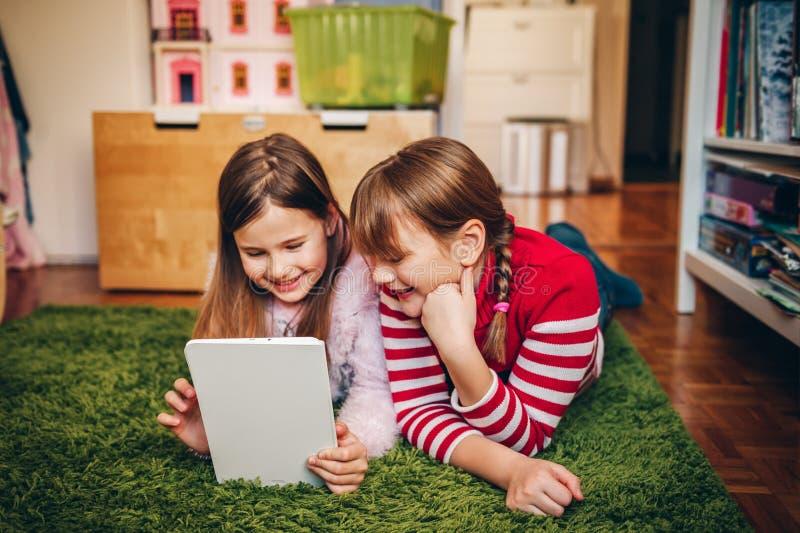 Duas meninas bonitos que jogam no PC digital da tabuleta fotos de stock