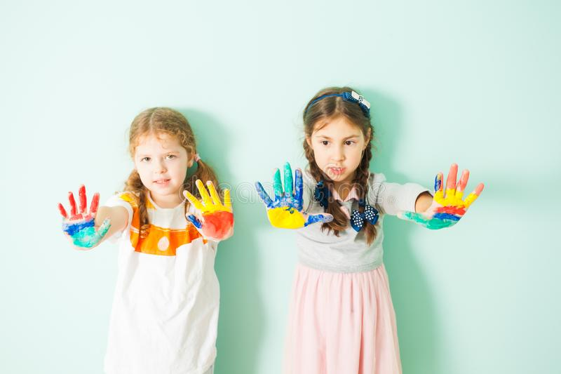 Duas meninas bonitos que mostram suas mãos pintadas fotografia de stock