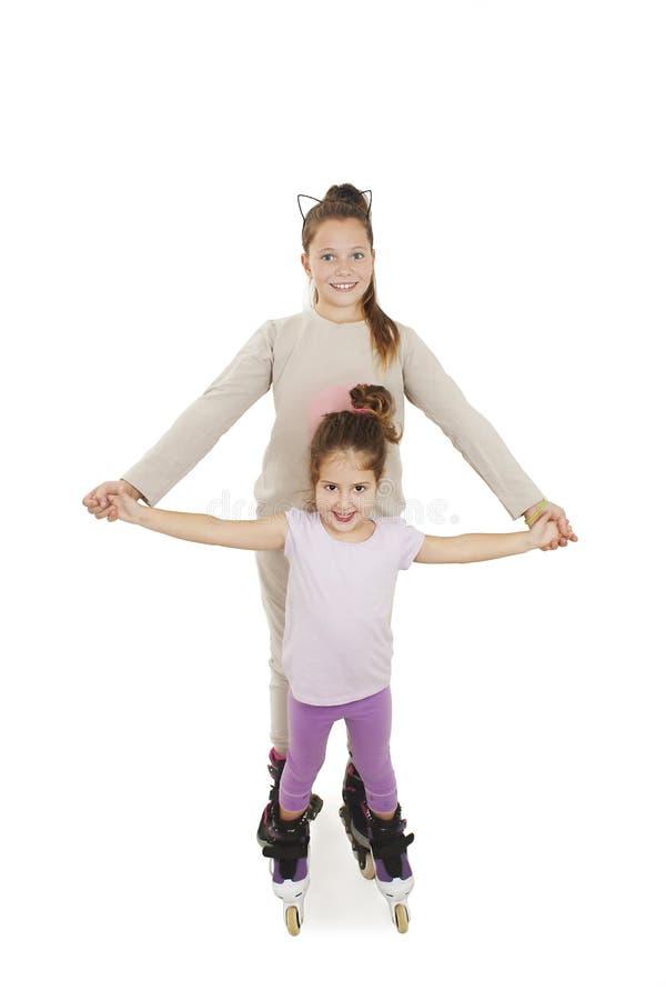Duas meninas bonitos que prendem as mãos que desgastam patins de rolo imagem de stock