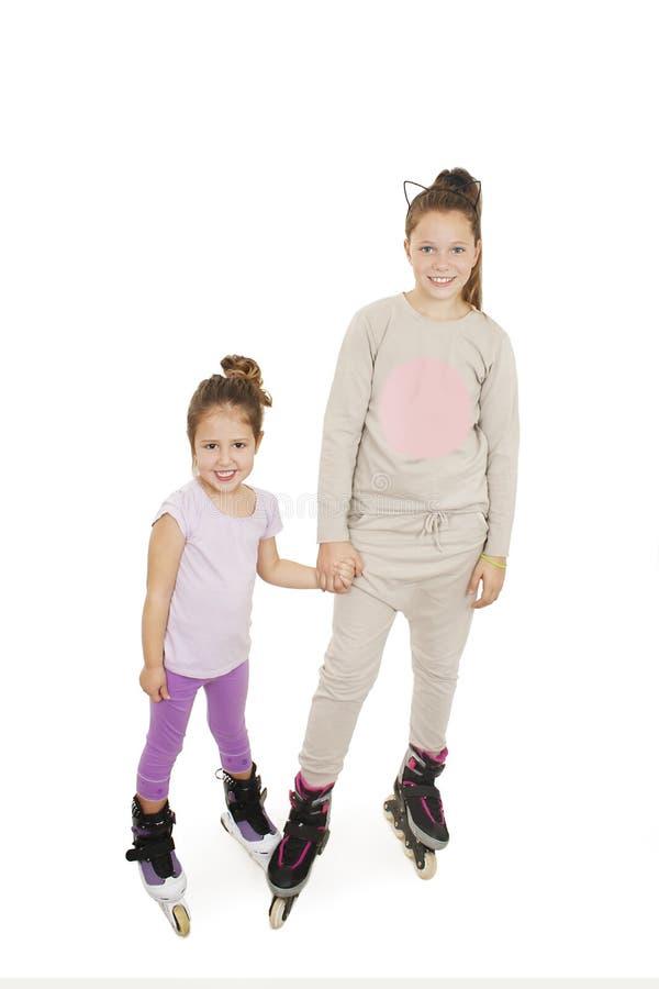 Duas meninas bonitos que prendem as mãos que desgastam patins de rolo foto de stock