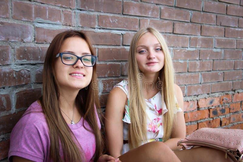 Duas meninas bonitos que sentam-se na frente de uma parede de tijolo fotografia de stock