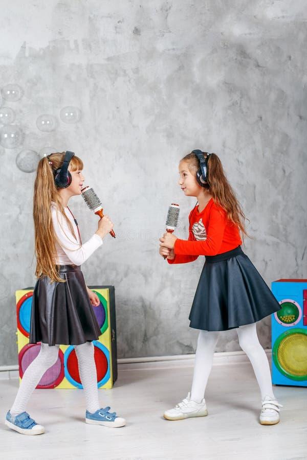 Duas meninas cantam e dançam O conceito é infância, lifes foto de stock