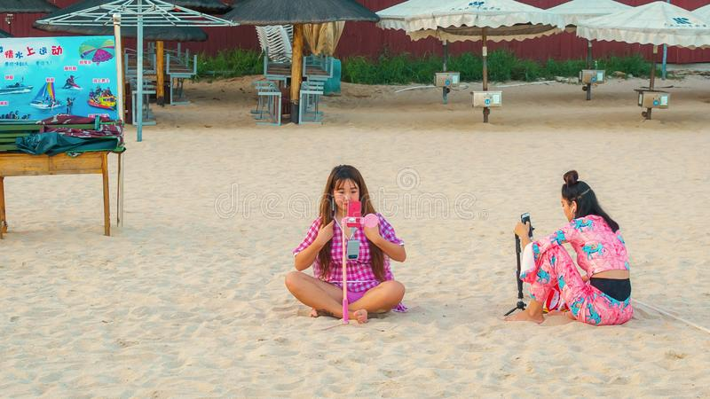 Duas meninas chinesas novas na praia, sentando-se na areia, tomam um selfie imagem de stock