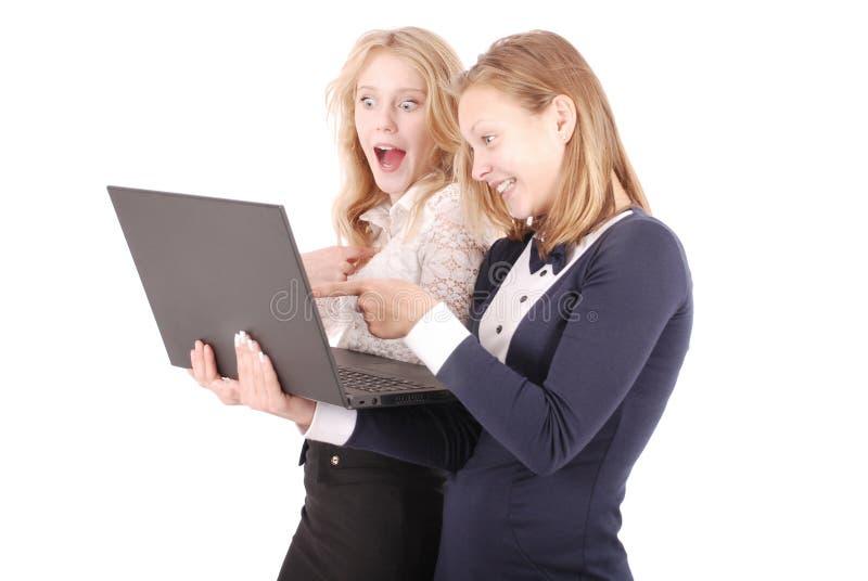 Duas meninas chocadas que usam o portátil fotografia de stock