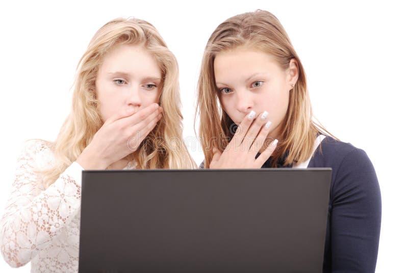 Duas meninas chocadas que usam o portátil foto de stock
