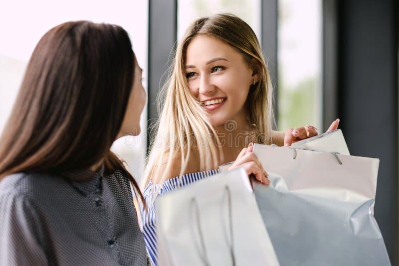 Duas meninas com a compra que senta-se em um banco na alameda imagens de stock royalty free