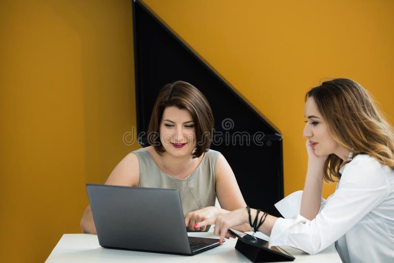 Duas meninas com o portátil na tabela foto de stock royalty free