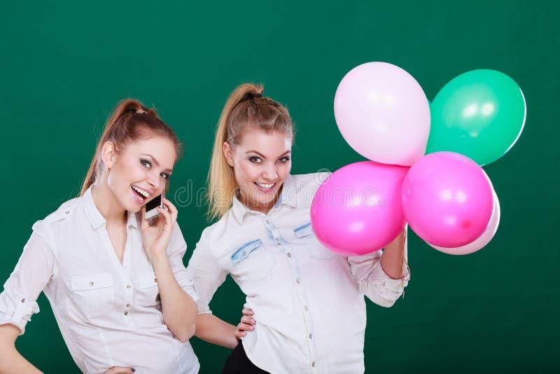 Duas meninas com telefone celular e bal?es fotografia de stock