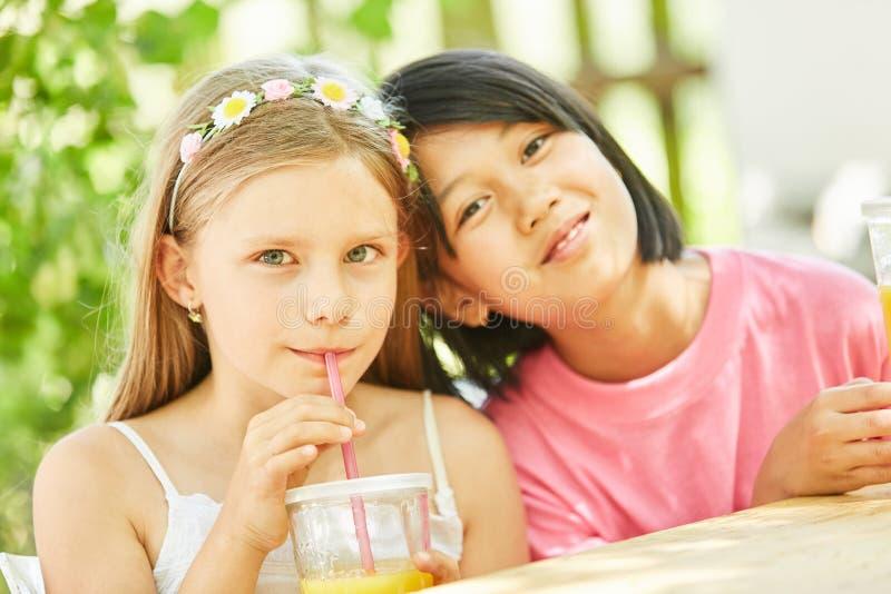 Duas meninas como as amigas bebem o suco fotografia de stock royalty free