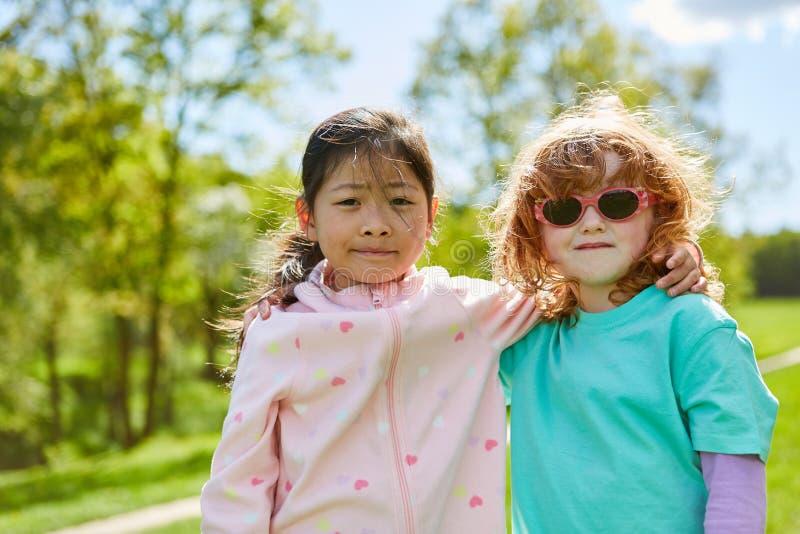 Duas meninas como as melhores amigas no parque imagens de stock royalty free
