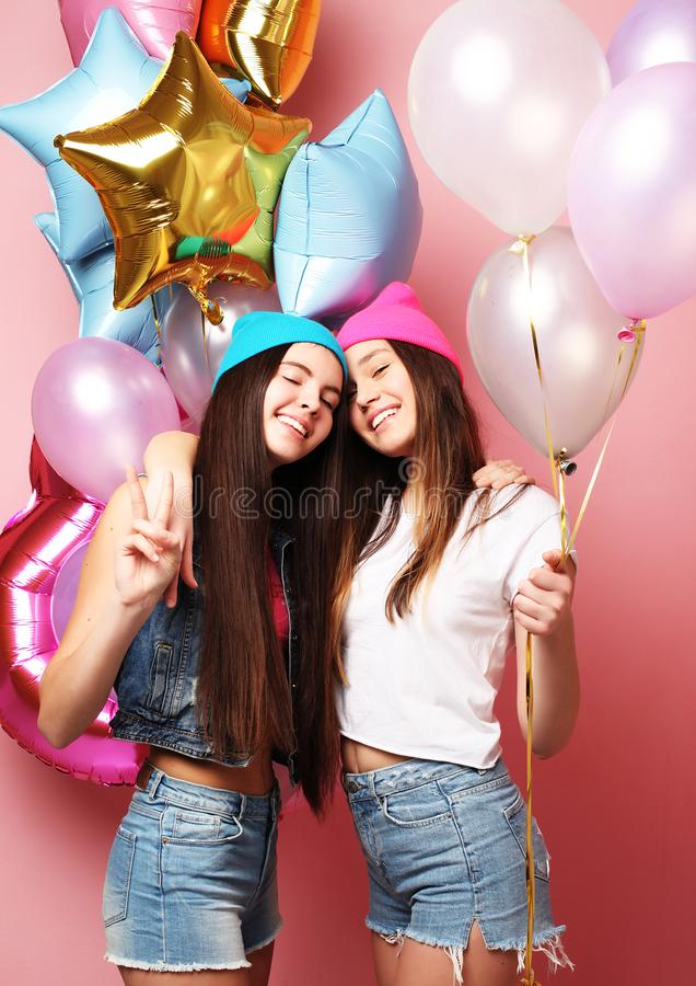 Duas meninas consideravelmente emocionais mantêm balões e levantamento contra o pino imagens de stock royalty free