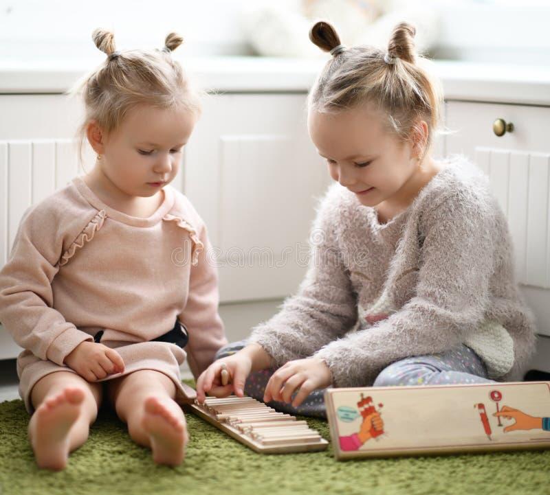 Duas meninas da criança jogam o jogo educacional no tapete verde em sua sala branca foto de stock royalty free