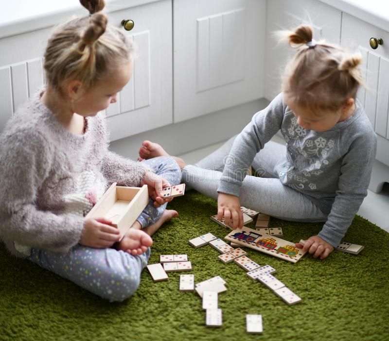 Duas meninas da criança jogam o jogo educacional no tapete verde em sua sala branca imagens de stock royalty free