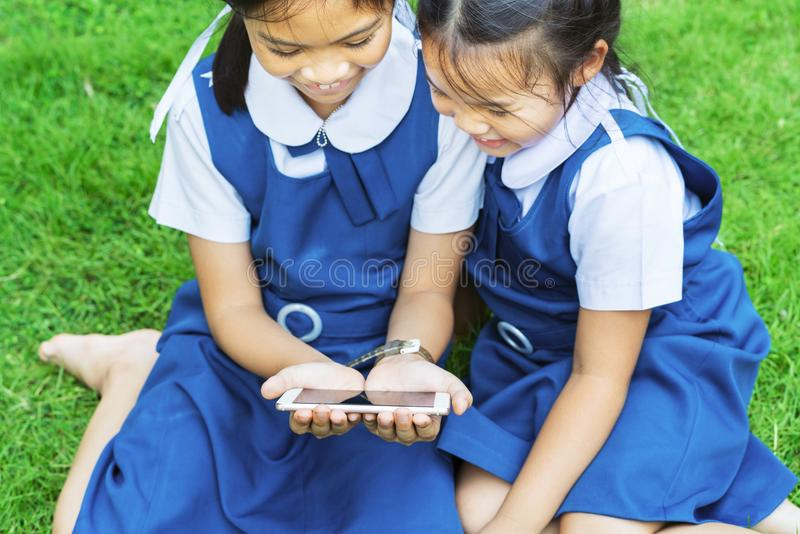 Duas meninas da irmã mais nova que jogam o Internet com o smartphone móvel na grama foto de stock
