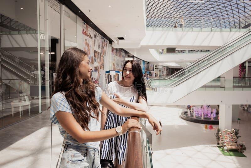 Duas meninas de cabelo escuro finas bonitos novas, suporte próximos um do outro em uma alameda moderna foto de stock royalty free