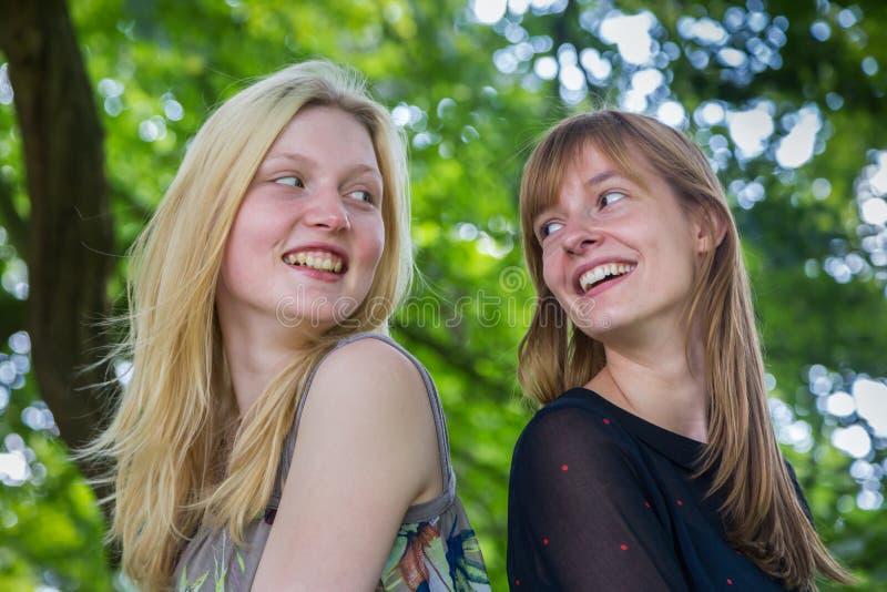 Duas meninas de cabelos compridos que riem entre si foto de stock royalty free