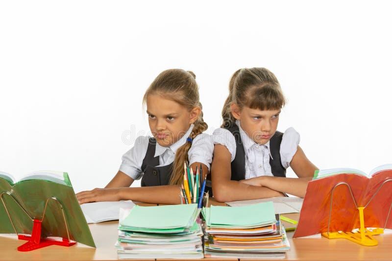 Duas meninas de discussão na mesma mesa foto de stock