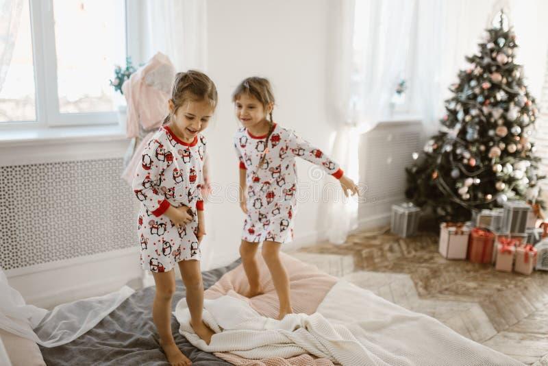 Duas meninas de encantamento em seus pijamas estão tendo o divertimento que salta em uma cama em um quarto acolhedor ensolarado  fotografia de stock royalty free