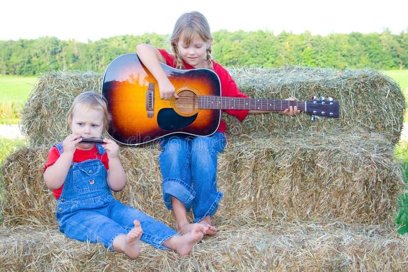 Duas meninas de exploração agrícola doces com instrumentos. imagens de stock royalty free