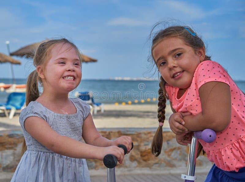 Duas meninas de sorriso em 'trotinette's pela praia imagem de stock