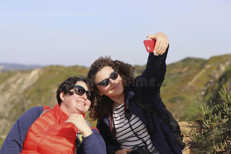 Duas meninas de sorriso em vidros de sol estão fazendo selfies contra um céu azul e umas montanhas verdes fotografia de stock