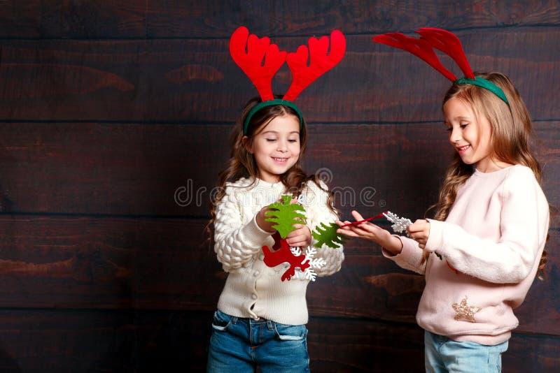 Duas meninas de sorriso pequenas com a grinalda do Natal em chifres dos cervos no fundo de madeira Feliz Natal e ano novo feliz imagens de stock