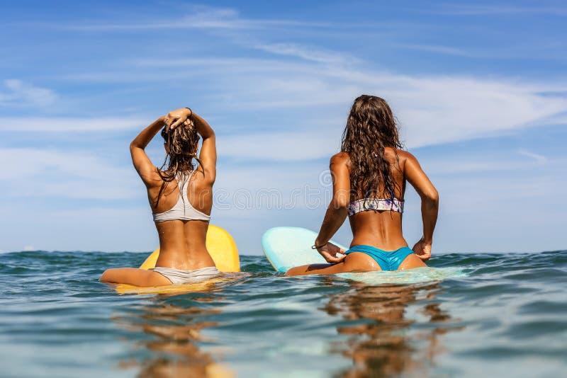 Duas meninas desportivas bonitas que surfam no oceano fotografia de stock