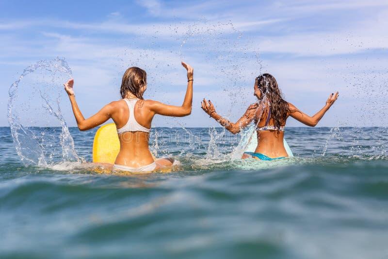 Duas meninas desportivas bonitas que surfam no oceano imagens de stock