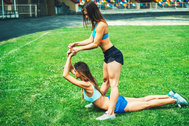 Duas meninas desportivas bonitos malham junto exterior fotografia de stock