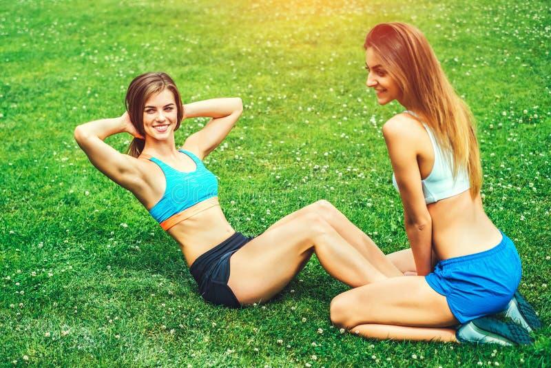Duas meninas desportivas bonitos malham junto exterior fotos de stock