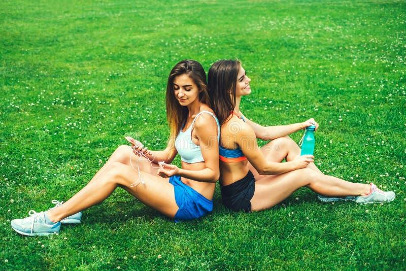 Duas meninas desportivas bonitos que relaxam após o exercício exterior fotos de stock