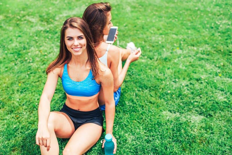 Duas meninas desportivas bonitos que relaxam após o exercício exterior imagens de stock