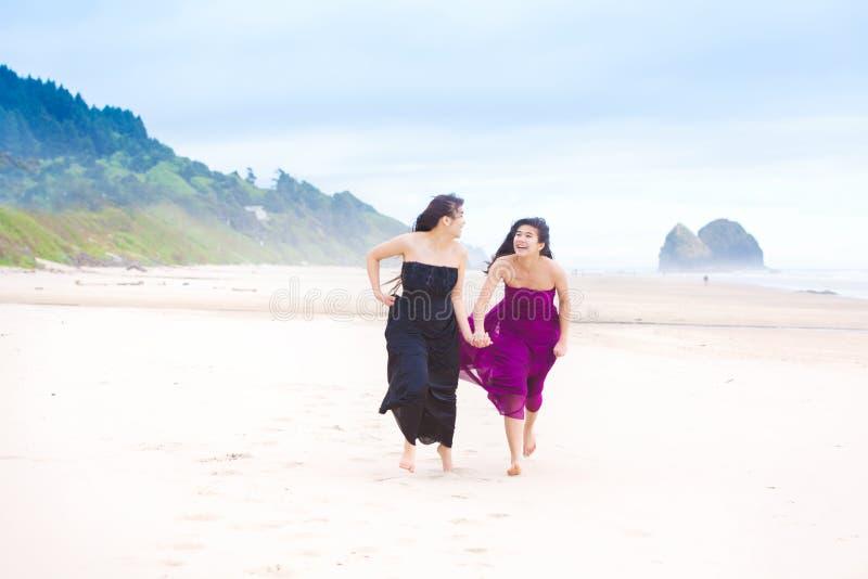 Duas meninas do adolescente que correm na praia no dia nebuloso fresco fotos de stock