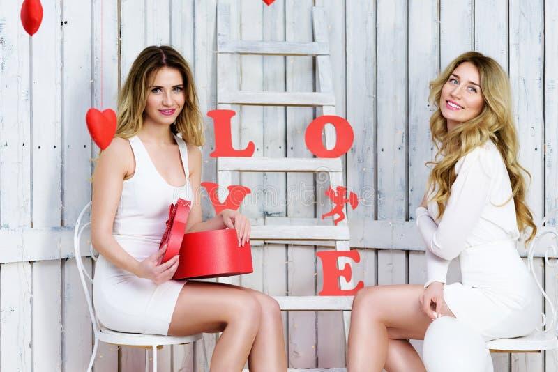 Duas meninas do anjo no branco vestem o dia de Valentim de sorriso imagem de stock royalty free