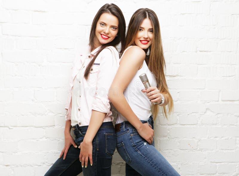 Duas meninas do moderno da beleza com um microfone imagem de stock royalty free