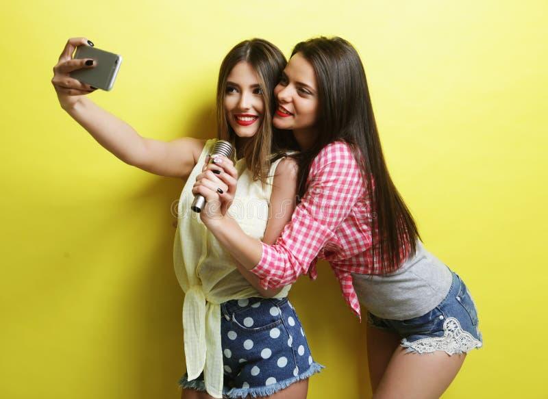 Duas meninas do moderno da beleza com um microfone tomam o selfi imagens de stock