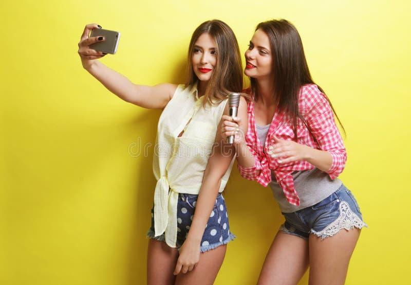 Duas meninas do moderno da beleza com um microfone tomam o selfi fotografia de stock